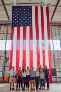 studnets in front of large flag